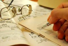 Scrivendo su un vecchio manoscritto musicale Immagini Stock Libere da Diritti