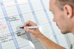 Scrivendo sul calendario murale Fotografie Stock