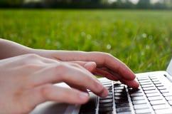 Scrivendo sul computer portatile in natura fotografia stock libera da diritti