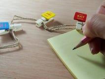 Scrivendo sulla carta per appunti con le graffette di legno come giorno piacevole, sabato Fotografie Stock Libere da Diritti