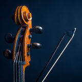 Scroll cello and fiddlestick. On dark background Stock Photo