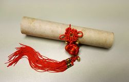Scroll with chinese knot. Old scroll with a red chinese knot on white background Royalty Free Stock Photography