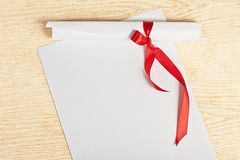 Scroll of paper with a red ribbon. Stock Photos