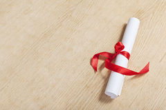 Scroll of paper with a red ribbon. Royalty Free Stock Photo