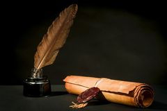 Scroll of a papyrus with a seal, a feather and an inkwell. A papyrus scroll with a seal, a feather and an inkwell on a black background royalty free stock photos