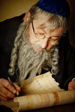 Scroll writing. Old jewish man with beard writing on a parchment scroll Stock Photo