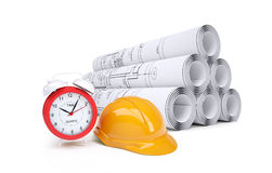 Scrolls of architectural drawings and alarm clock Stock Photo