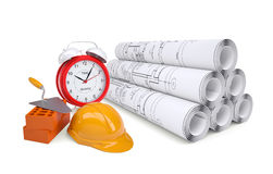 Scrolls of architectural drawings and alarm clock Royalty Free Stock Photos