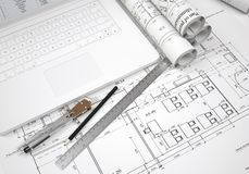 Scrolls architectural drawings and laptop Stock Photography