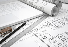 Scrolls architectural drawings and laptop Royalty Free Stock Photos