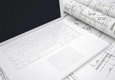 Scrolls of architectural drawings and laptop Royalty Free Stock Image