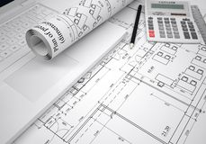 Scrolls of architectural drawings and laptop Stock Image