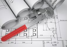 Scrolls of architectural drawings and pipe wrench Stock Images