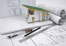 Scrolls architectural drawings and small house. Architect concept Royalty Free Stock Images