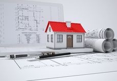 Scrolls architectural drawings and small house. Architect concept Stock Photos