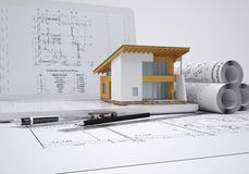 Scrolls architectural drawings and small house. Architect concept Stock Images