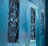 Scrollwork on Teal Blue Doors. Historic New Orleans  building with blue doors and antique ironwork Stock Image