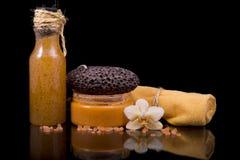 Scrub и сливк тела, оранжевое полотенце Terry, цветок орхидеи и море Стоковое Фото