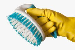 Scrub brush. Close up of a isolated hand wearing a yellow cleaning glove holding a scrub brush over white Royalty Free Stock Images