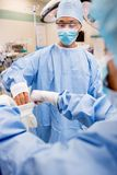 Scrub Nurse Helping Surgeon with Sterile Glove Royalty Free Stock Images