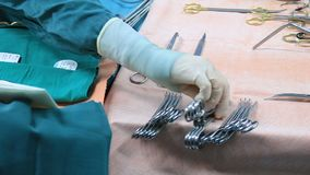 Scrub nurse preparing tools for operation. Closeup of gloved hand taking steralized surgery instrument. Scrub nurse preparing surgical instruments for operation stock video
