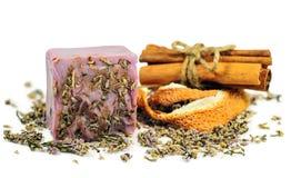 Scrub soap bar. Violet scrub soap bar at cinnamon and orange peel background isolated on white stock photos