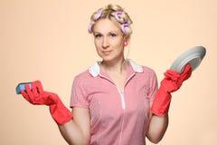 Αστεία νέα νοικοκυρά με τα γάντια που κρατά scrubberr Στοκ Φωτογραφίες