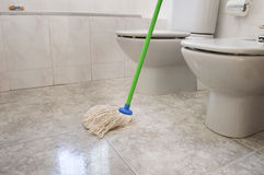 Scrubbing bathroom with a mop gray Royalty Free Stock Image