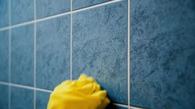 Scrubbing the tiles in the kitchen with a sponge stock video footage