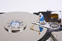 Scrubbing the Hard Drive. Miniature woman with broom works on hard drive Royalty Free Stock Photo