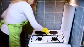 Scrubbing the stove in the kitchen with a sponge stock footage