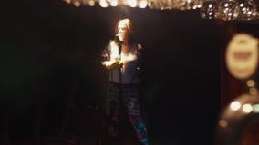 Scrubwoman canta in scena in microfono sotto il riflettore grido Capelli di scossa archivi video