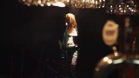 Scrubwoman nas luvas canta na fase no microfone do vintage sob o projetor dança filme