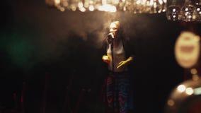 Scrubwoman nas luvas canta na fase no microfone do vintage sob o projetor Fumo filme