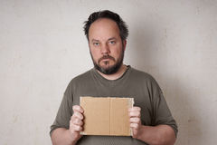 Scruffy man holding sign. Grubby scruffy man holding blank cardboard sign Stock Photo
