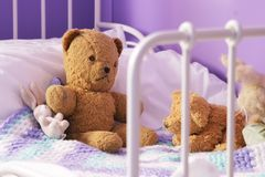 Scruffy old teddy bears on a child's bed. Slightly dog-eared old (1960s) stuffed toys on a small child's bed Stock Photo