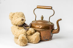 Scruffy teddy bear with copper kettle on white background Royalty Free Stock Image