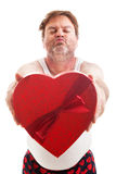 Scruffy Valentine Guy Ready for Kiss. Humorous photo of a scruffy looking middle aged man in his underwear holding a box of Valentines day candy and waiting for Royalty Free Stock Photos