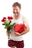 Scruffy Valentines Guy in Underwear. Humorous photo of a scruffy looking middle aged man in his underwear holding a bouquet of roses and a box of Valentines day royalty free stock photography