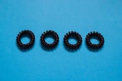 Scrunchies espirales plásticos del pelo en el fondo azul, concepto femenino de la muchacha de la belleza fotos de archivo