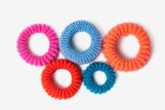 Scrunchy hair fall form olympiad isolate. Multicolored eraser for hair in the shape of symbols of the Olympics lie on a white background Royalty Free Stock Image