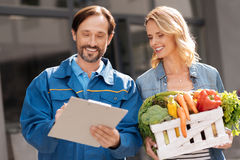 Scrupulous professional courier checking with the list Royalty Free Stock Photography