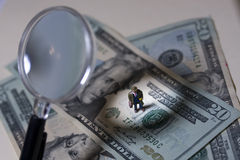 Scrutiny. Business man under scrutiny standing on US Currency Royalty Free Stock Photos