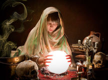 Scrying with a crystal ball. Beautiful young gypsy reading the future in a crystral ball Royalty Free Stock Photo