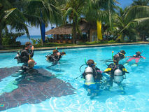 Scuba dive class adventure. A group of scuba divers learning how to dive in a class held in a tropical swimming pool stock photo