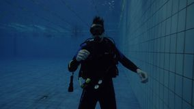 Scuba dive instructor showing hand gesture for underwater communication. At diving course in deep pool. Scuba diver training on diving lesson in swimming pool stock video footage