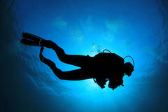 Scuba Diver. In blue ocean, silhouette against sun stock photo