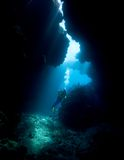 Scuba Diver. A female scuba diver in an underwater cave with sunbeams Royalty Free Stock Photos