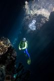Scuba Diver. A pretty female scuba diver in a cave with sunbeams Royalty Free Stock Images