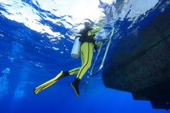 Scuba diver and boat. Scuba diver climb the ladder of the dive boat Stock Image